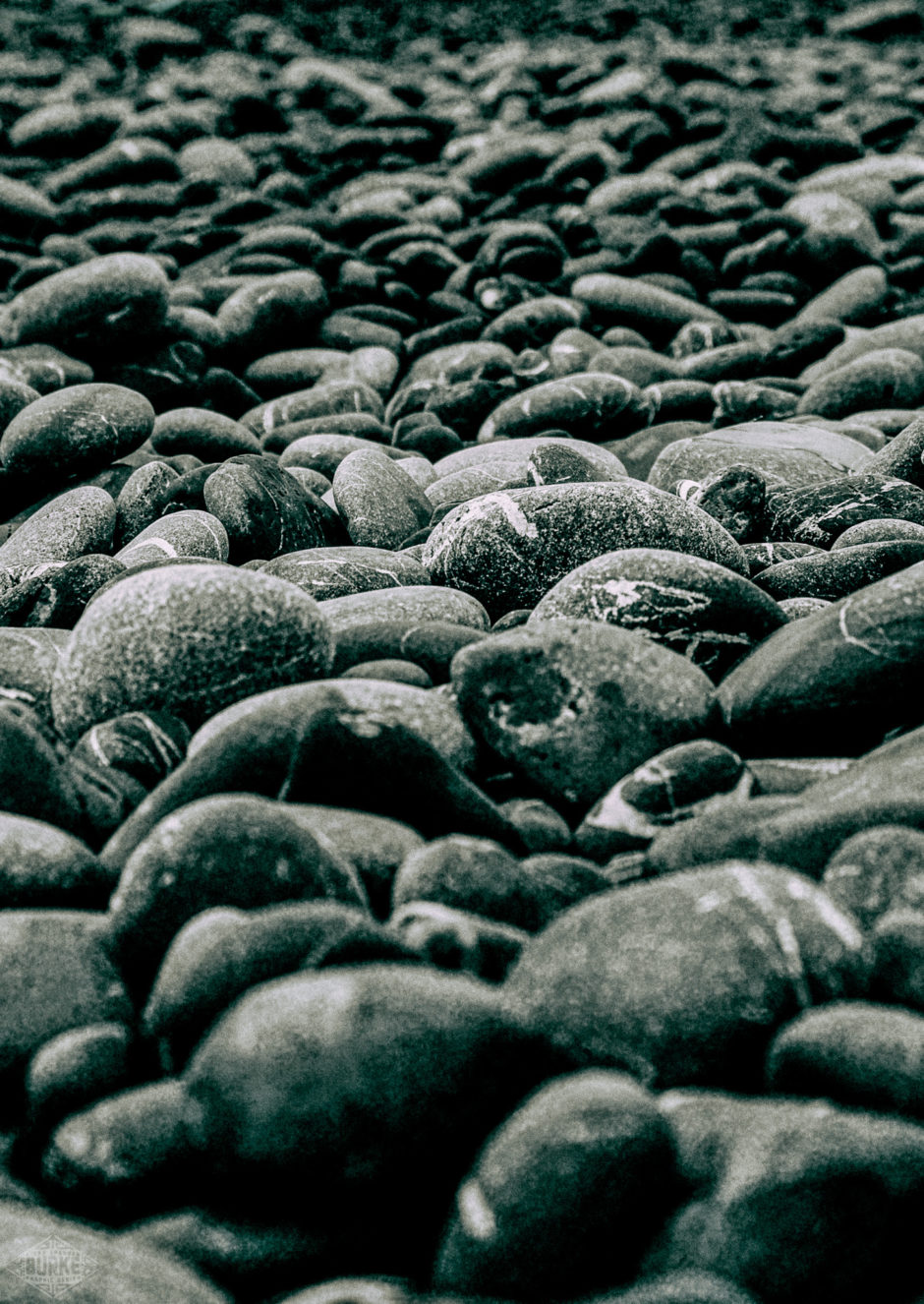 The 'sand' of Black Sands Beach in Shelter Cove, California is made up of these rounded rocks striated with quartz.
